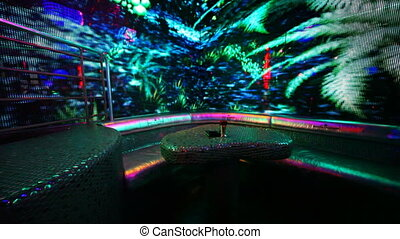 table and sofa in nightclub with bright LED illumination on walls