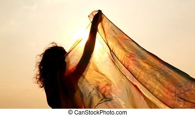 woman has hold thin shawl which waves on wind so it gets to...
