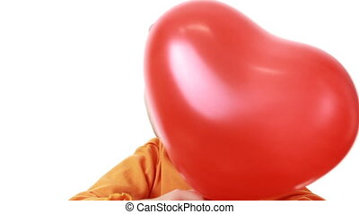 little girl hiding behind heart shaped balloon
