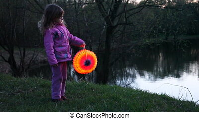 little girl hold ball from paper at night near lake - cute...