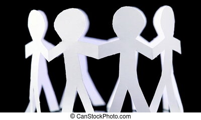 eight paper people stand in circle and hold hands, rotates...