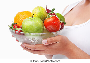 Woman holding a bowl of fruits