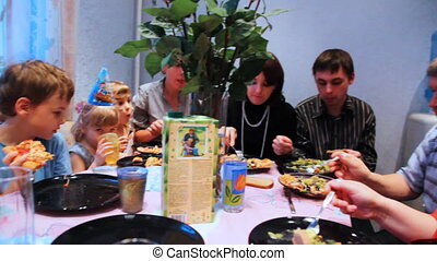family and many children with guests sit around table,...