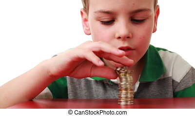 boy takes off coins placed column and puts it on red base,...