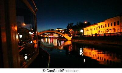 boat moves along Moscow River to small arched bridge