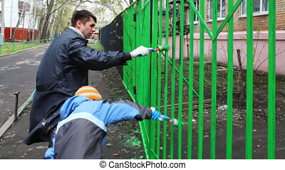 little boy and father in hand carefully dye fence on community work day