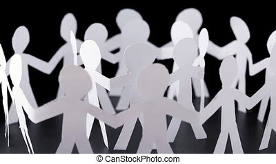 paper people stand in two circles and hold hands, rotates on...