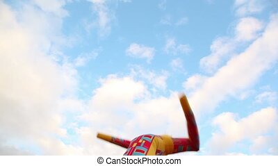 Colorful inflated man dance at background of sky with clouds