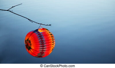 paper ball hang on branch above lake - colorful bright paper...
