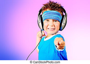 little dancer - Portrait of a cute boy listening to music on...