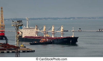 Cargo ship leaving port with tugs assistance