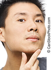 Asian man looking his unshaved chin - Close up portrait of...