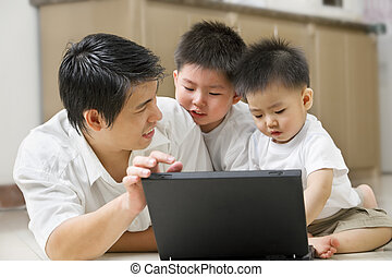Father introduce technology to his sons using laptop in home