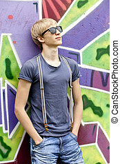 Style teen boy with in sunglasses near graffiti background