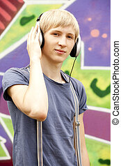 Style teen boy with headphones near graffiti background