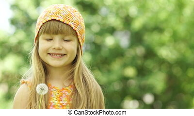 3s girl blowing a dandelion. Close-