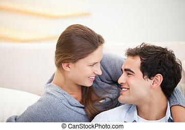 Couple looking each other while embracing in a sitting room