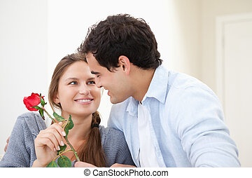Man offering a rose to a Woman while embracing indoors