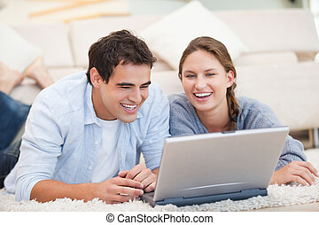 Young Couple lying while using a computer in a sitting room