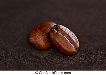Two coffee beans side by side - Two coffee beans on a black...