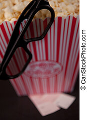 Glasses hanging on the edge of a box of pop corn