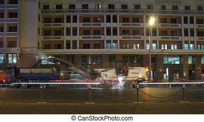 Steamroller stacks asphalt at night on highway in city