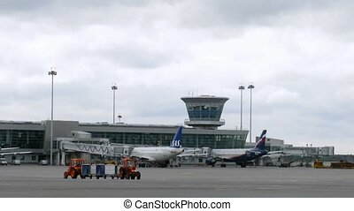 Two planes SAS and AEROFLOT stand in front of control tower...