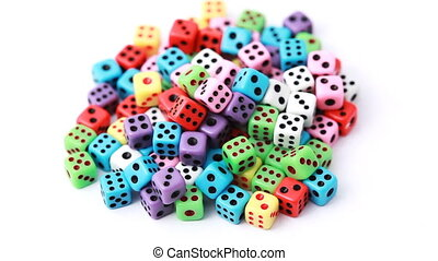 many colorful dice stacked in pile rotate on white