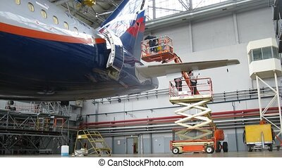 Flight mechanics spend checkup of plane Aeroflot in hangar...