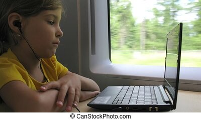 Girl watch video on notebook while travelling by train, time...