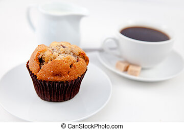 Muffin and a cup of coffee on white plates with sugar and...
