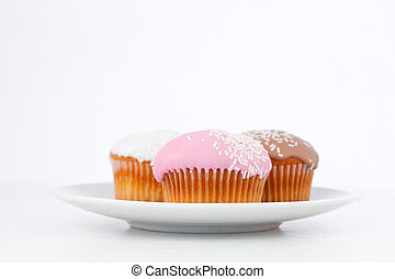 Muffins with icing sugar on a white plate against a white...