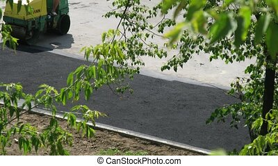 Worker stacks asphalt by steamroller AMMANN on road - MOSCOW...