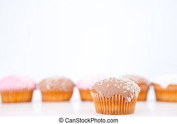 Muffins with icing sugar placed in line against a white...