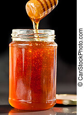 Honey sticky trickle dropping in a jar against a black...