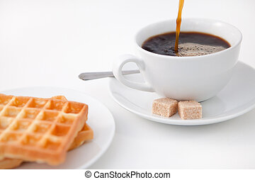 Waffles sugar and a cup of coffee on white plate against a...