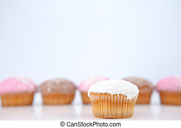 Muffin placed in front of a line of muffin with icing sugar...