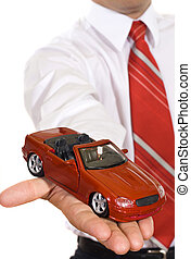 Car loan offer - Businessman handing over a new red toy car...