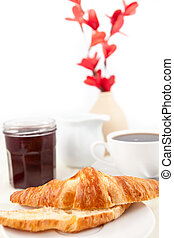 Breakfast with a bisected croissant against white background...