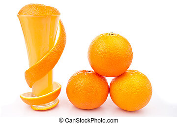 Orange peel wrapped around a glass near a pile of oranges