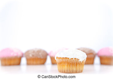 White muffin placed in front of a line of muffin with icing...