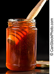 Honey full jar with a honey dipper against a black...