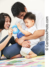 Asian young family spending time together, playing with...