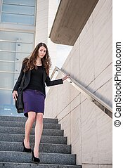 Business woman walking in hurry on stairs