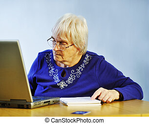 On-Line Shopping - senior woman buying something on-line