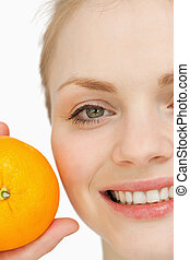 Close up of a cheerful woman holding an orange against white...