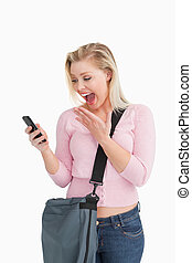 Happy woman showing her surprise while reading a text...