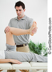 Brunette physiotherapist manipulating a leg in a room