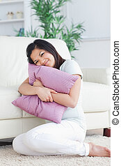 Woman holding tight a pillow in a living room