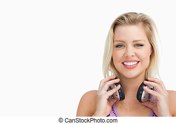 Peaceful blonde woman holding her headphones against a white...